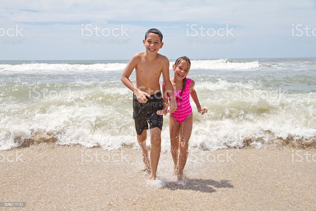 Brother and sister running from the sea stock photo