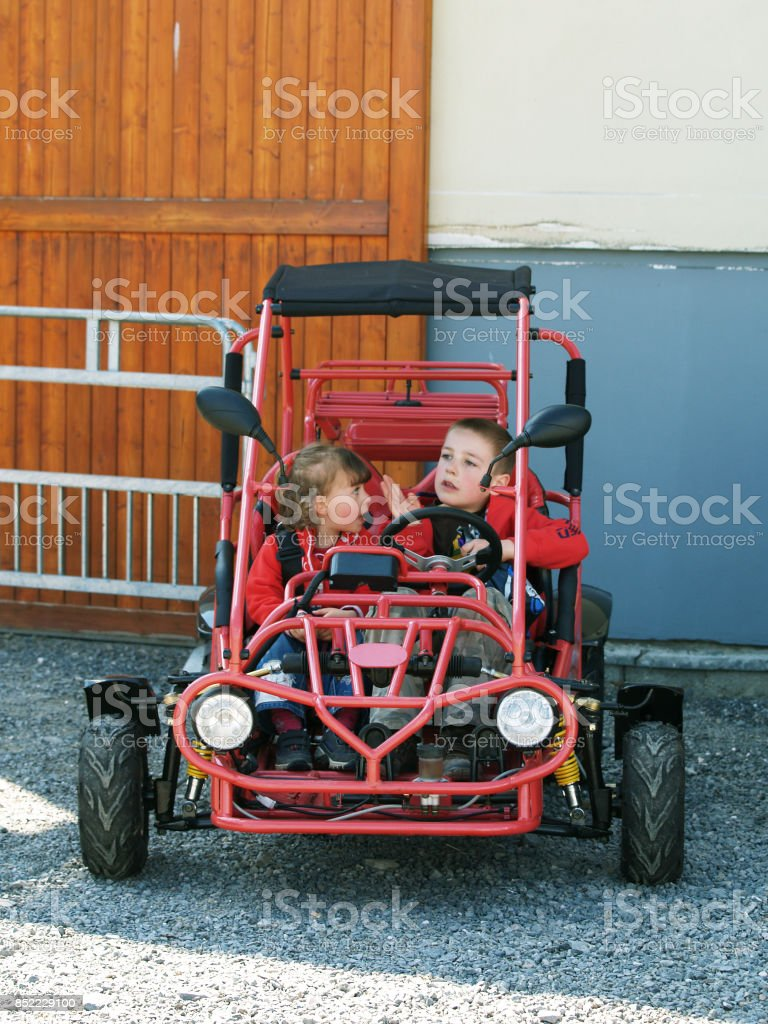 Brother and sister sitting in buggy stock photo
