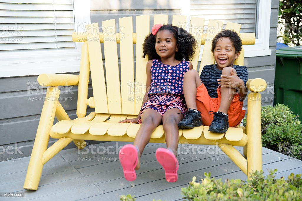 Brother and sister sitting on yellow bench, smiling stock photo