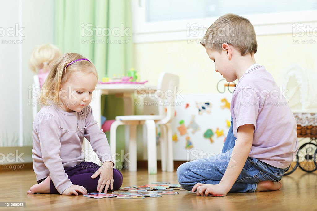 Brother and sister solving puzzle stock photo