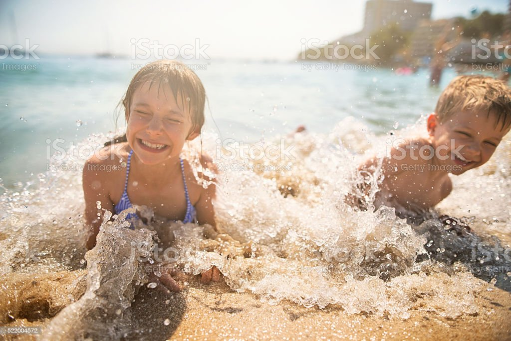 Brother and sister spashed by waves stock photo
