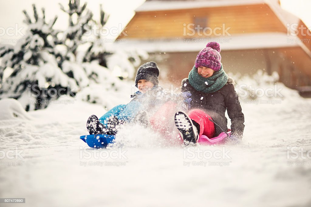 Brother and sister tobogganing in winter forest stock photo