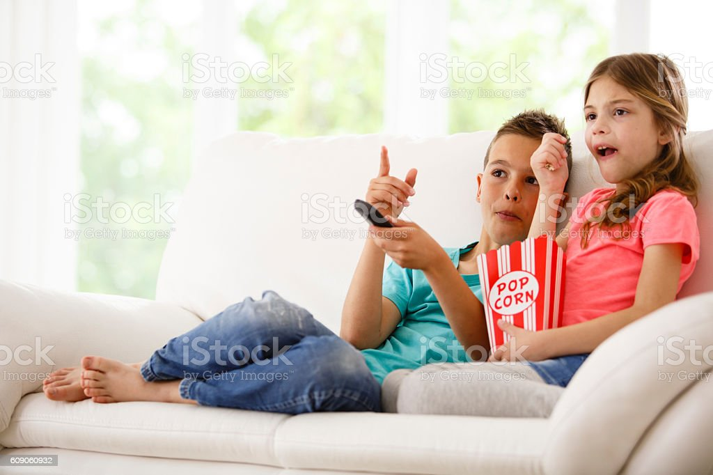Brother and sister watching television stock photo