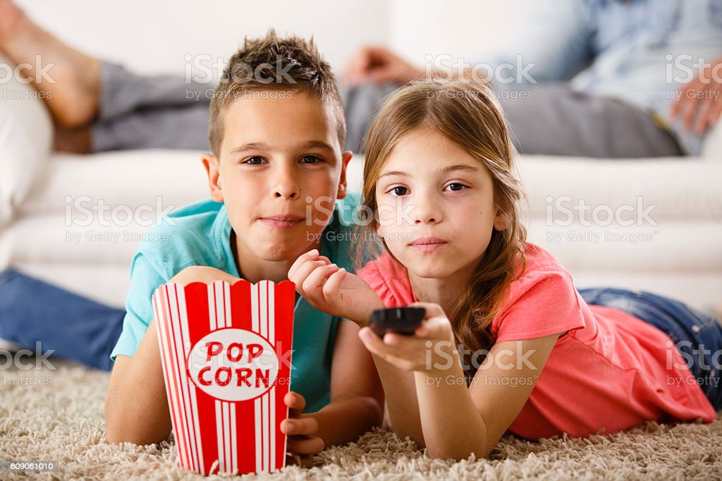 Brother and sister watching TV stock photo