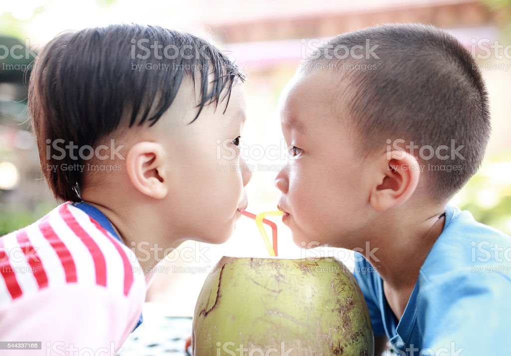 Brother drinking coconut stock photo
