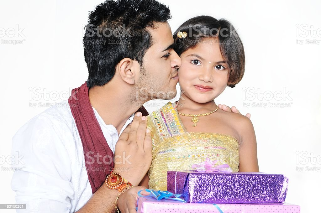 Brother giving gift to his little sister over white background. stock photo