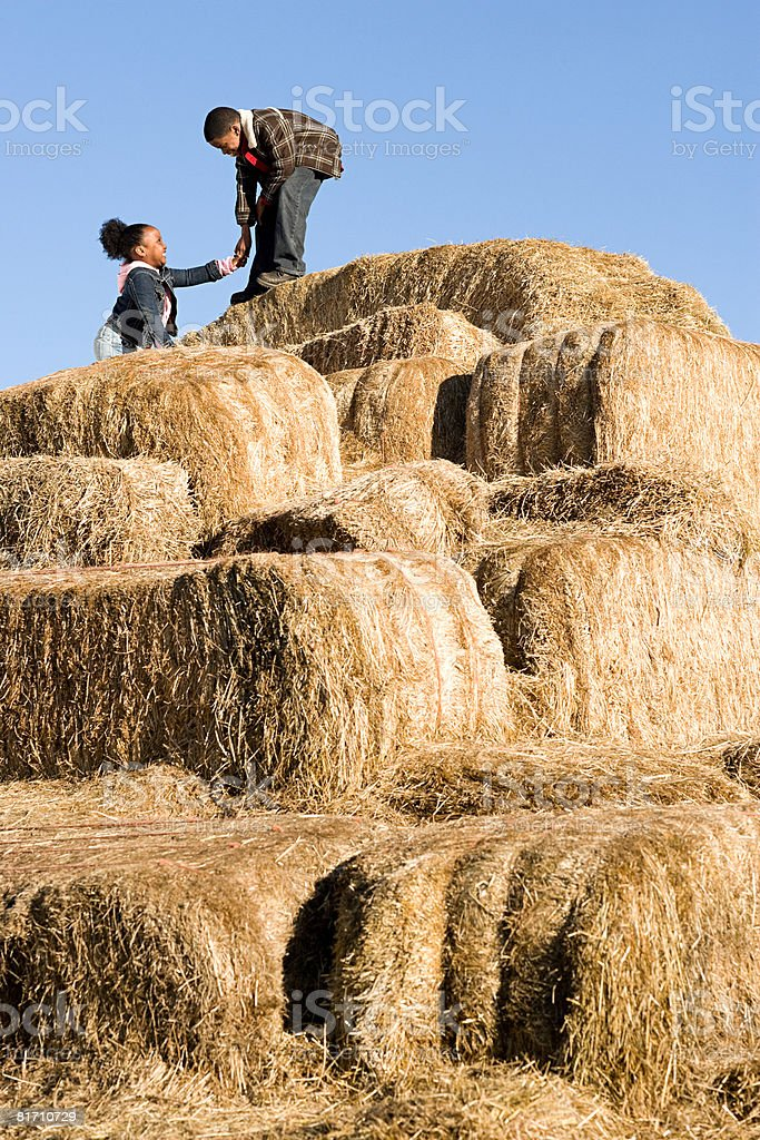 Brother helping his sister climb bales of hay royalty-free stock photo