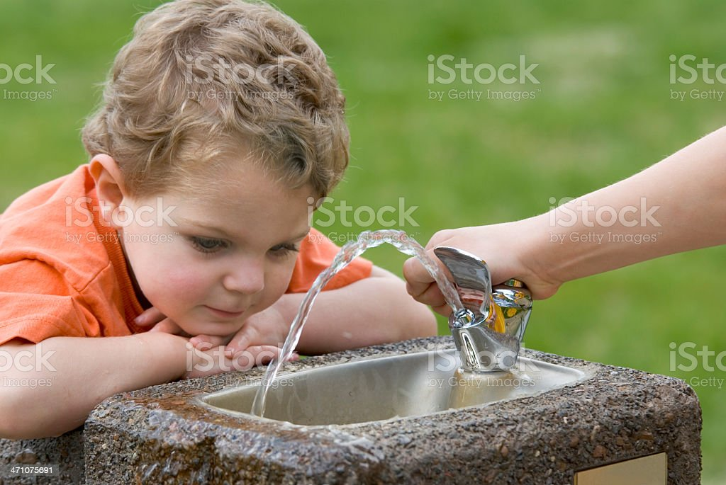 Brother Helps Toddler With Drinking Fountain royalty-free stock photo