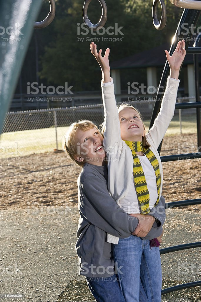 A brother is lifting his sister to the playground rings royalty-free stock photo