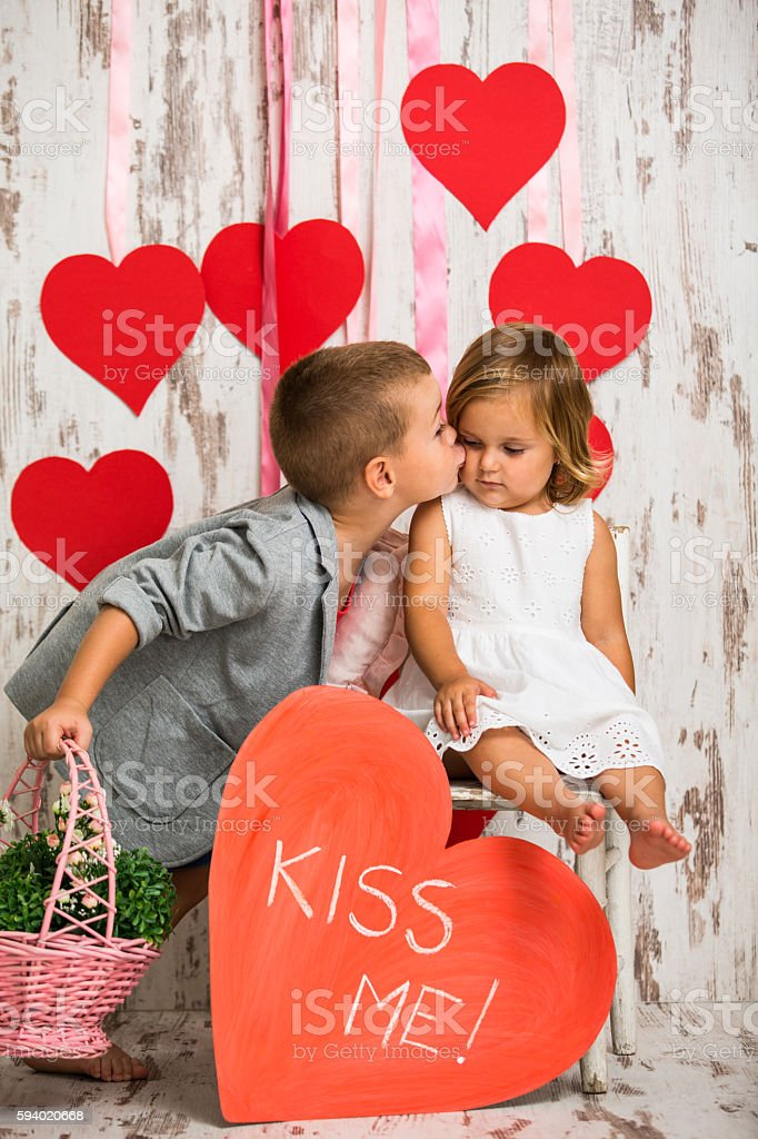 Brother kissing his little sister stock photo