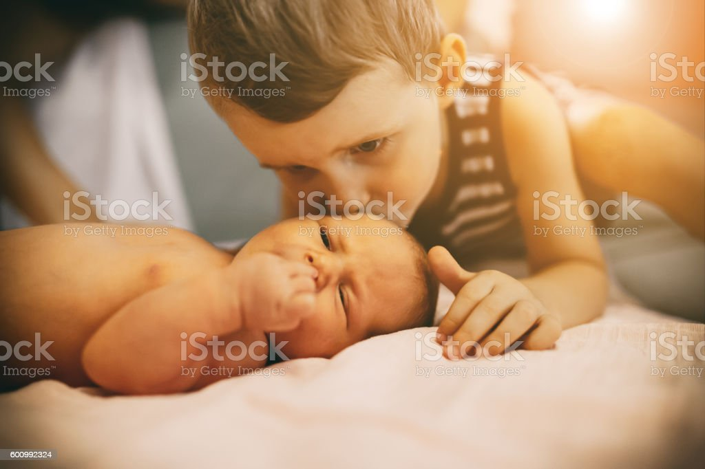 Brother kissing little newborn sister stock photo