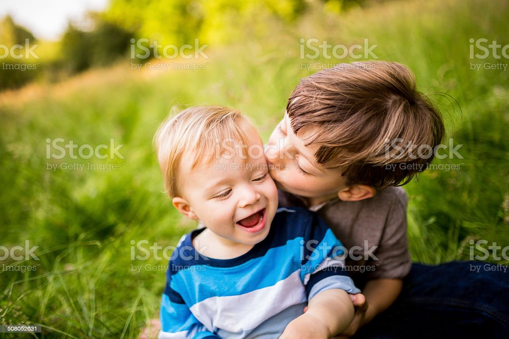 Brother kissing sibling on Cheek stock photo