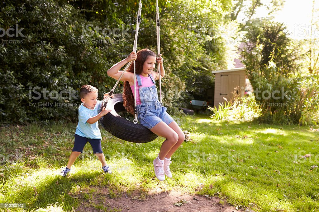 Brother Pushing Sister On Tire Swing In Garden stock photo