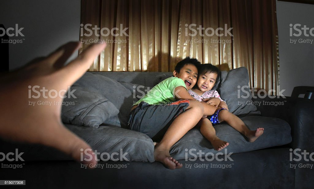 brother sister fear scary hand in living room stock photo