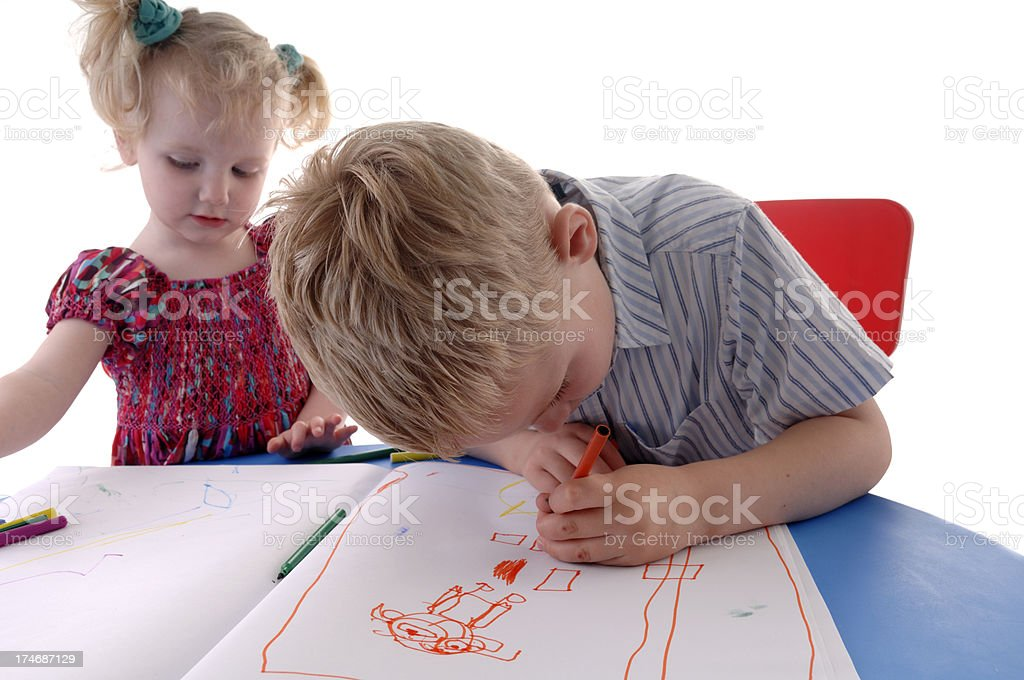 brotherdrawing a picture while his sister looks on royalty-free stock photo