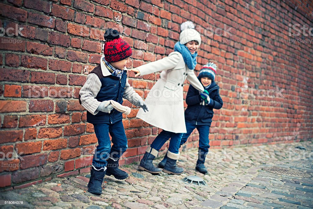 Brothers and sister playing near warsaw old town castle wall stock photo