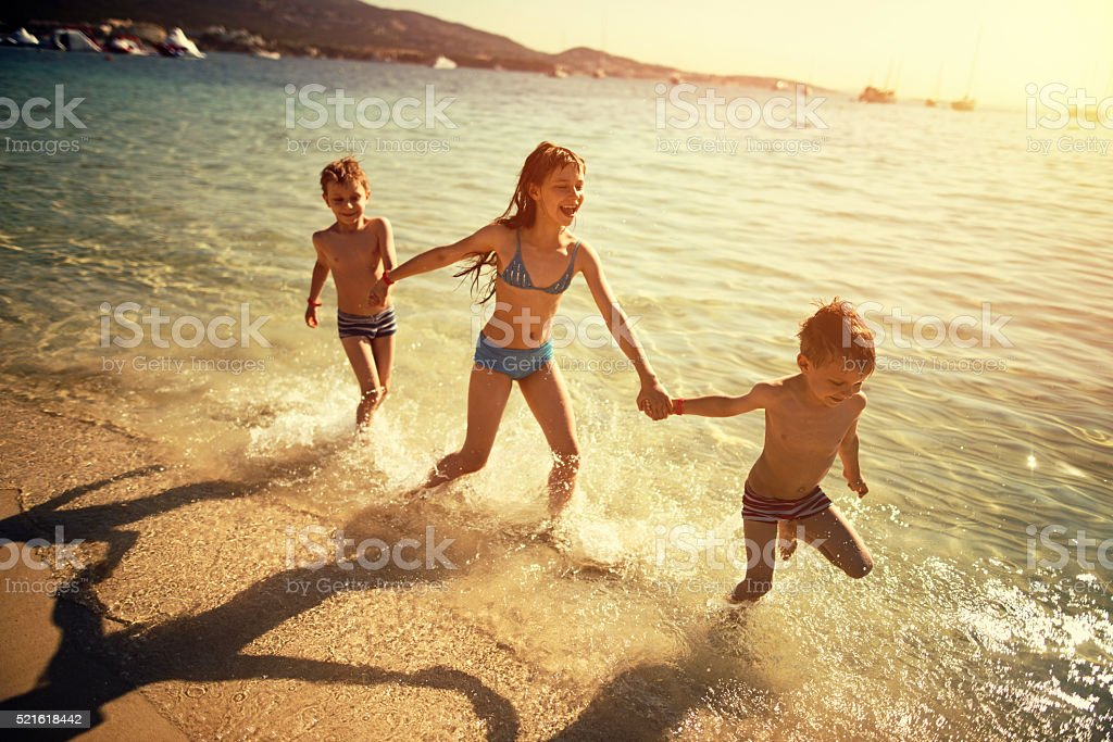 Brothers and sister running on beach laughing stock photo