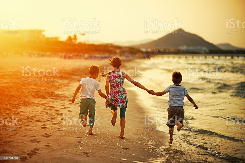 Brothers and sister running on beach on sunset stock photo