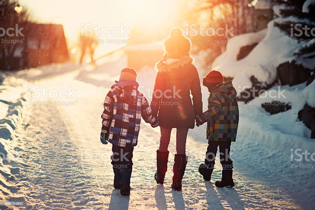 Brothers and sister walking on road on sunny winter evening. stock photo