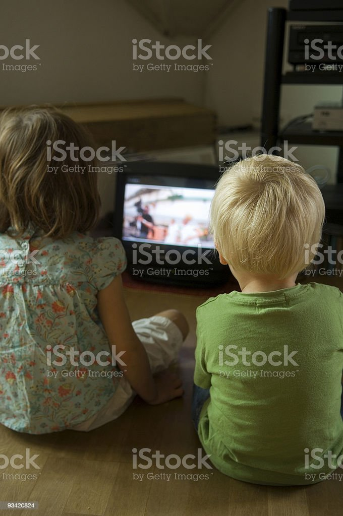 brothers and sisters watching television royalty-free stock photo