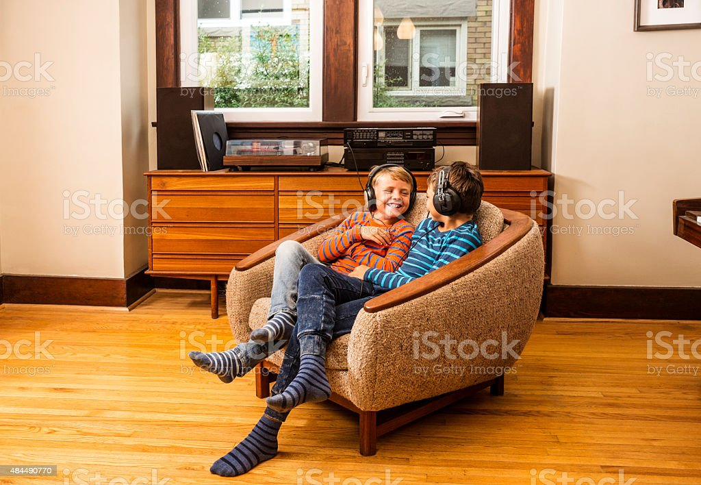 Brothers hanging out listening to music stock photo