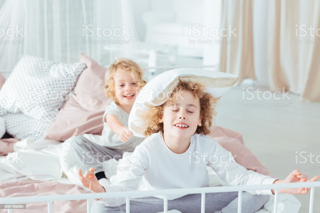 Brothers having morning pillow fight stock photo