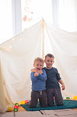 Brothers Hugging in Improvised Tent Cheerfully