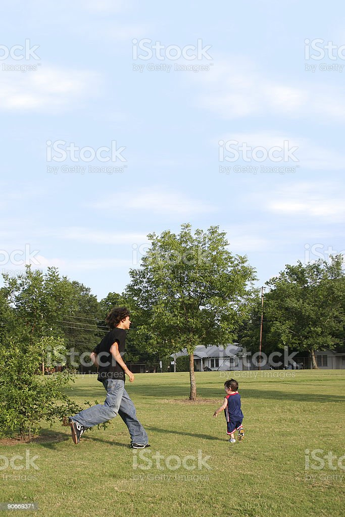 Brothers Playing Chase At The Park royalty-free stock photo