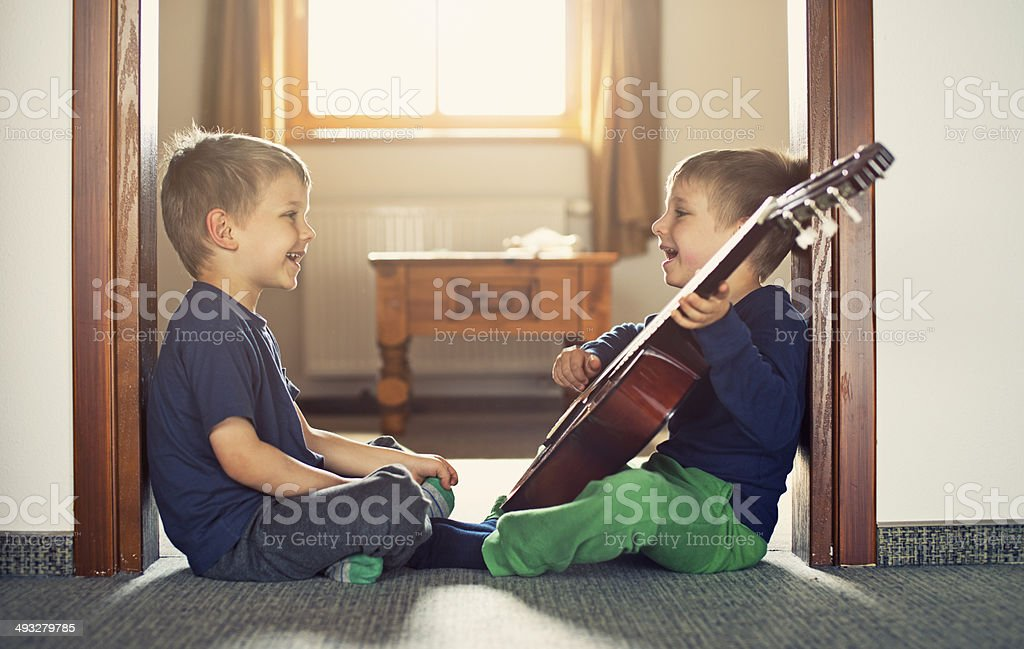 Brothers playing the guitar and singing stock photo