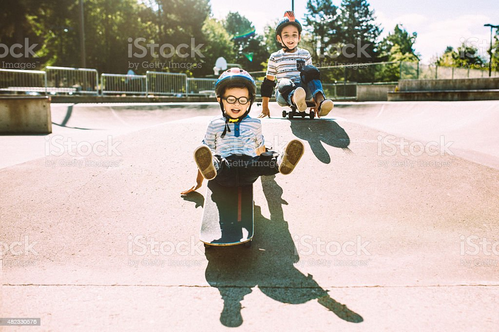 Brothers Riding Skateboards at Park stock photo