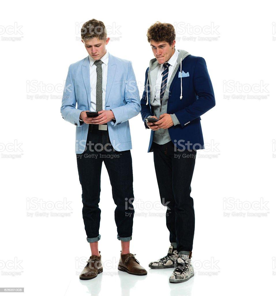 Brothers using phone stock photo