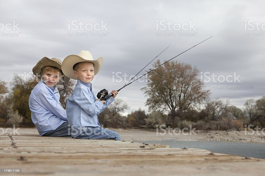 Brothers Wearing Cowboy Hats Sitting and Fishing royalty-free stock photo