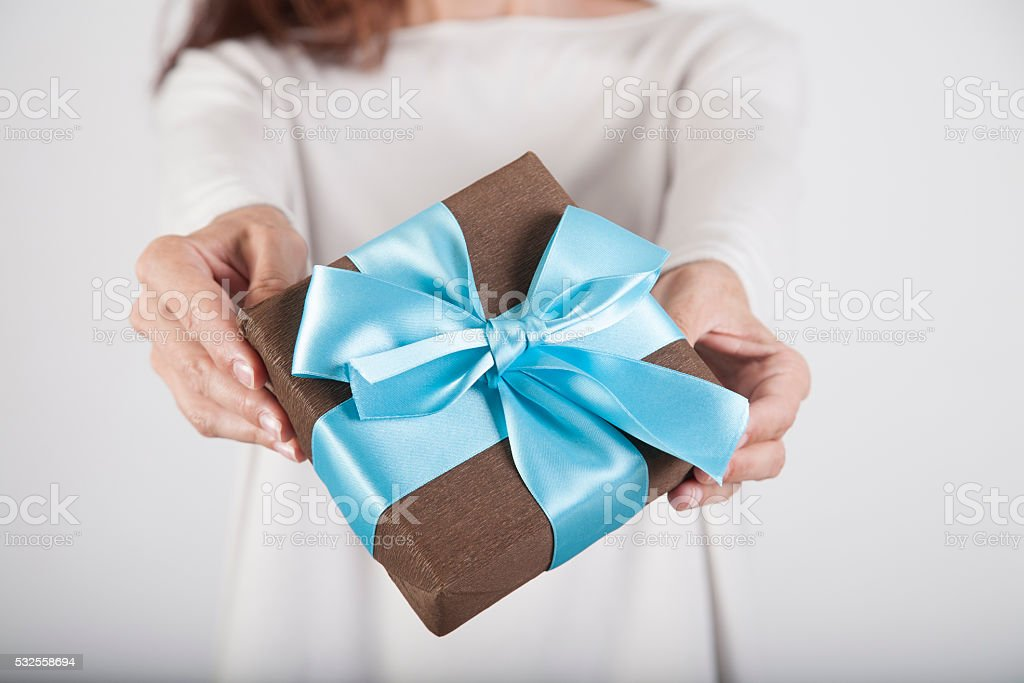 brown and blue gift in woman hands stock photo