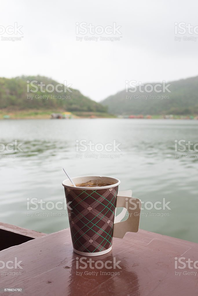 brown and hot coffee cup in morning with river view Стоковые фото Стоковая фотография