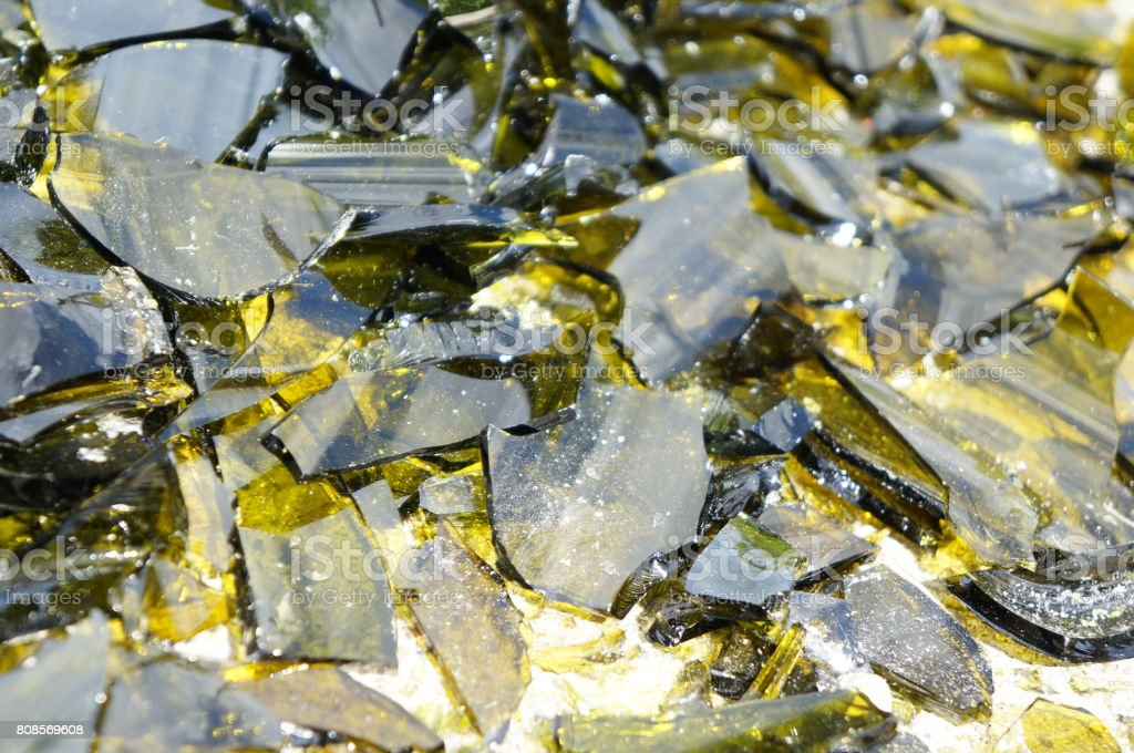 Brown and yellow broken glass in the rays of the bright sun stock photo