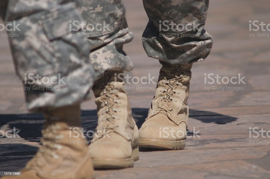Brown army cadet boots with camouflage pants tucked in stock photo
