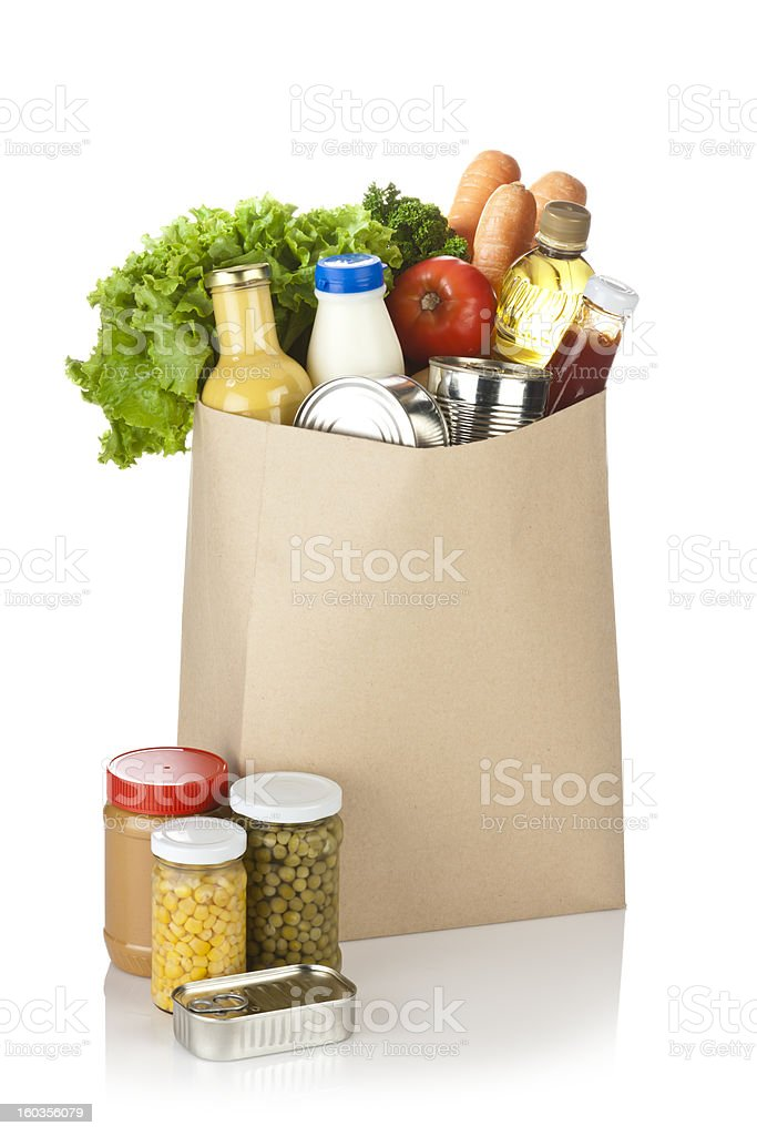 Brown bag full of groceries sits on white background royalty-free stock photo
