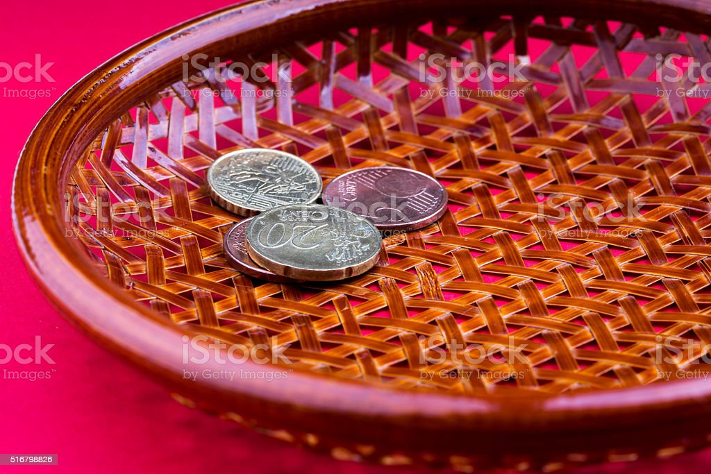 Brown basket on its side with few coins stock photo