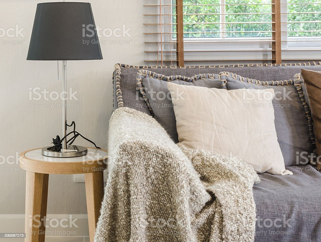 brown blanket on sofa with lamp in living room stock photo