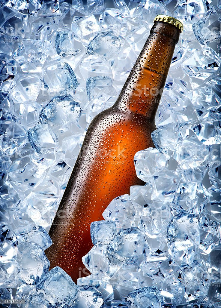Brown bottle in ice stock photo