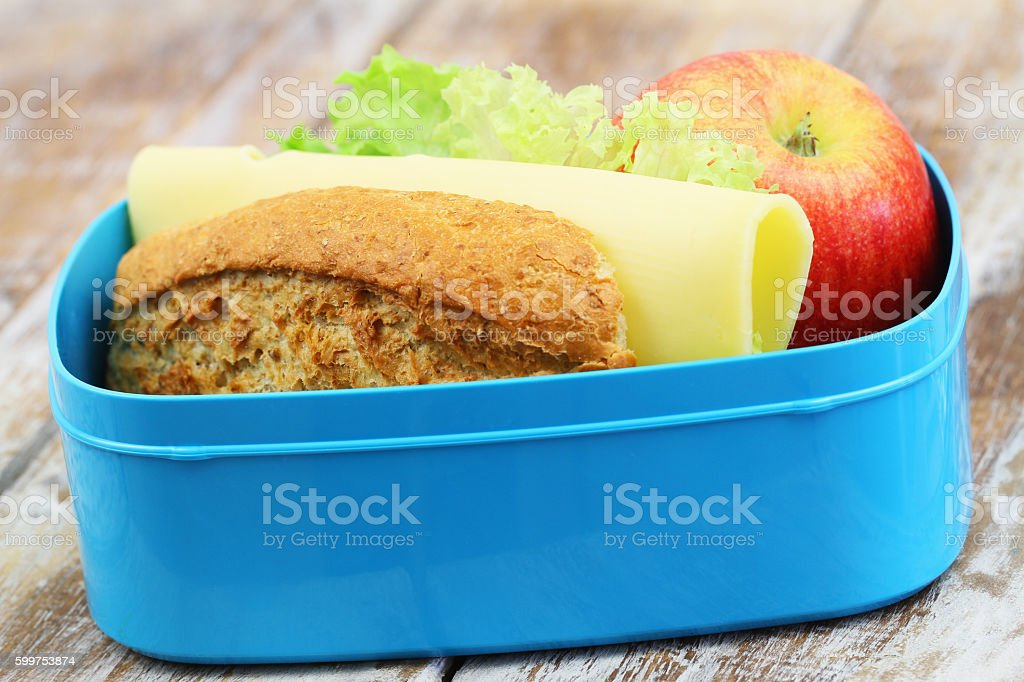 Brown bread cheese sandwich with lettuce, red apple in lunchbox stock photo