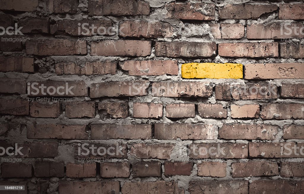 Brown brick wall with one gold brick stock photo