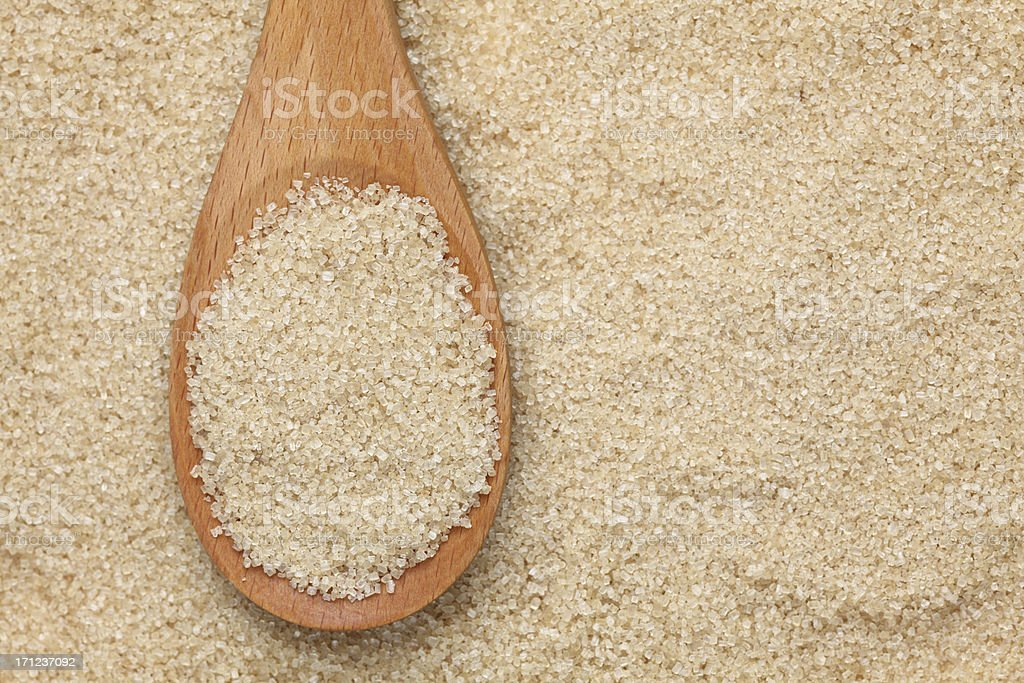 Brown cane sugar in a wooden spoon royalty-free stock photo