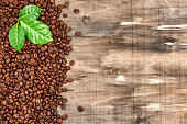 Brown coffee beans green leaves wooden background