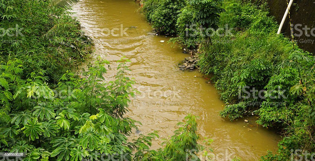 brown coloured dirty river in Bogor indonesia stock photo