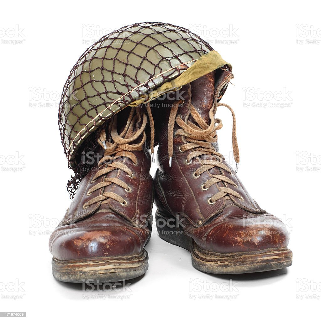 Brown combat boots and green army helmet stock photo