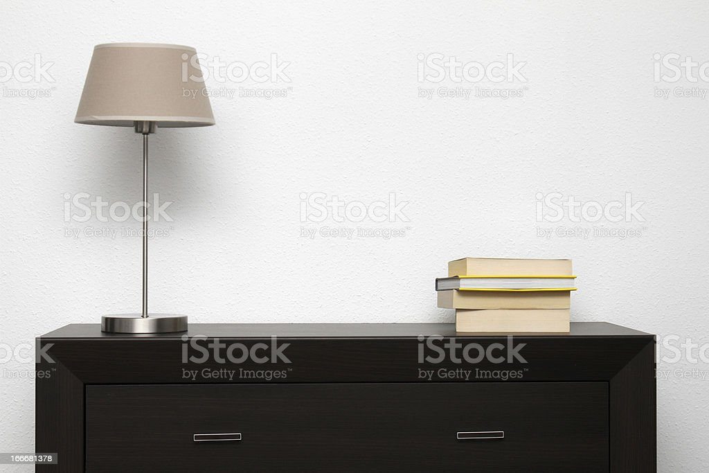 brown commode with lamp and books stock photo