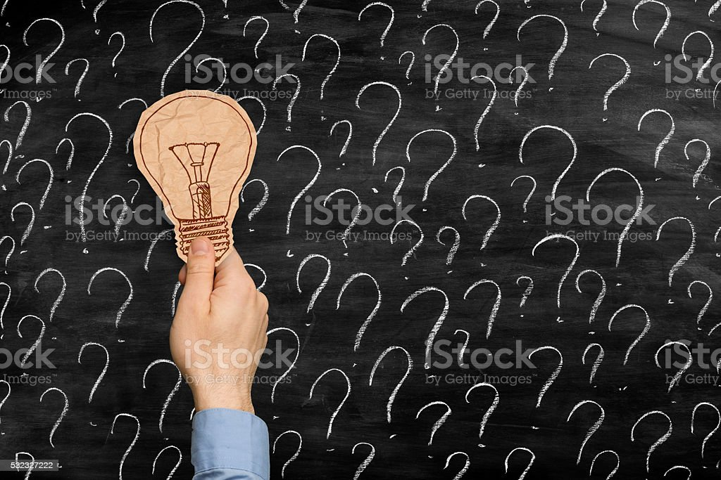 brown crumpled paper bulb on top of question marks stock photo