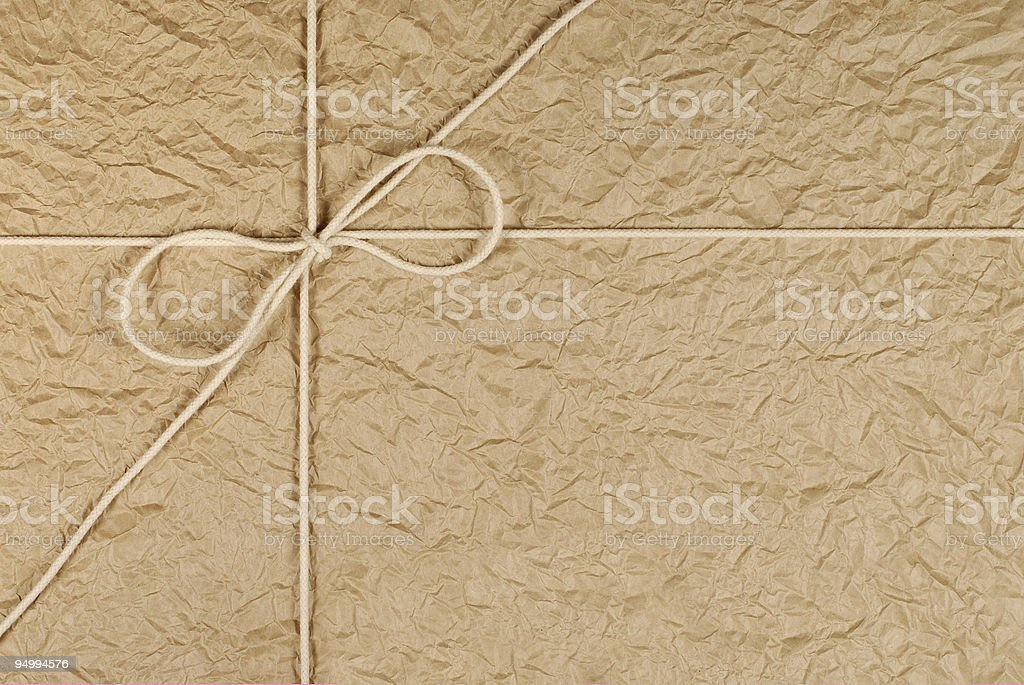 Brown crumpled parcel with rope royalty-free stock photo