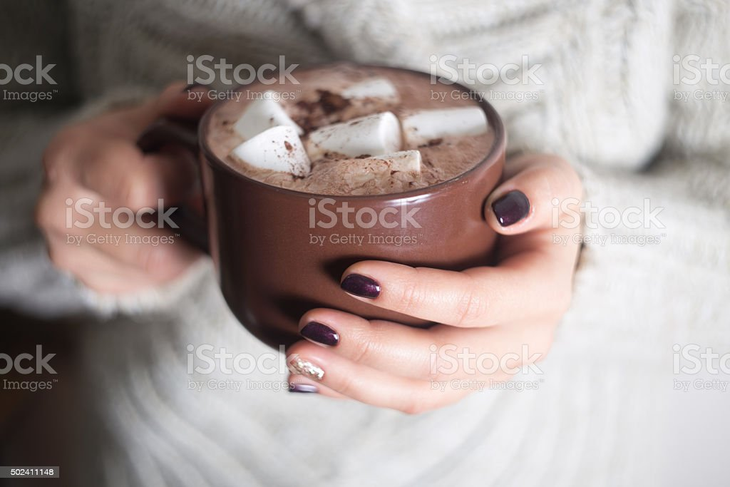 Brown cup with cocoa and marshmallow in the hands stock photo
